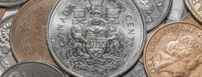 Pile of Canadian coins with silver half dollar on top
